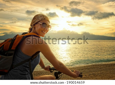 Young woman with backpack standing on the shore near his bike and smiling. - stock photo
