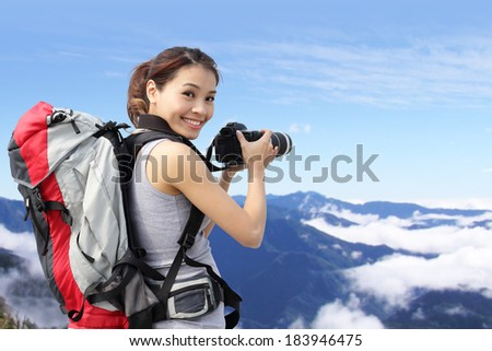 Young woman with backpack taking a photo on the top of mountains, asian - stock photo