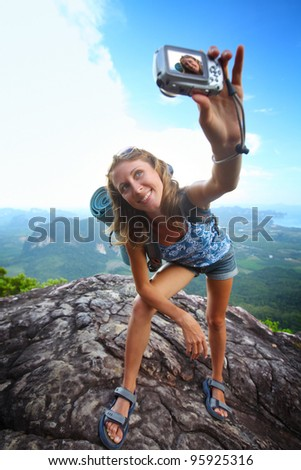 Young woman with backpack taking herself photo on top of a mountain - stock photo