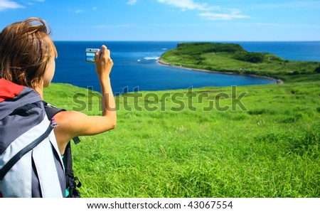 Young woman with backpack taking photo of a nature - stock photo