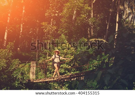 Young woman with backpack walking across hanging bridge above the river in green forest (intentional vintage color and sun glare) - stock photo