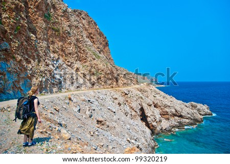Young woman with backpack walking  alley along the sea - stock photo