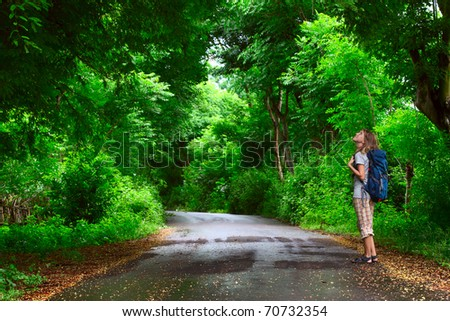 Young woman with backpack walking in park's asphalt road and looking to a trees