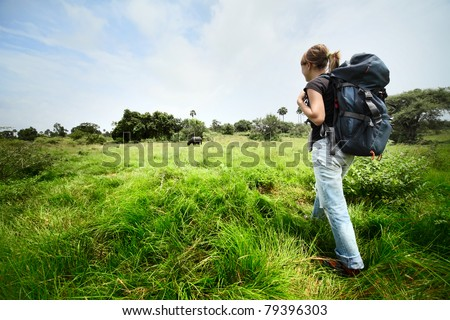 Young woman with backpack walking through a wild territory and looking to an animal