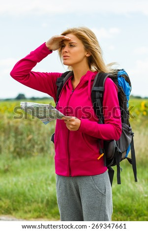 Young woman with backpacke is holding a map and looking which way to go.Where am I?  - stock photo