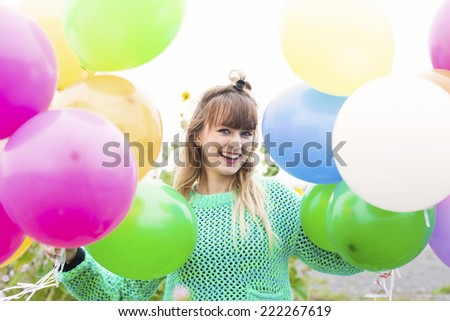 young woman with balloons on a field of flowers