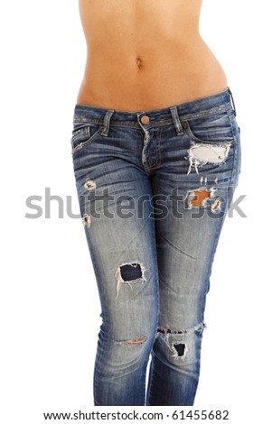 Young woman with bare top wearing worn jeans - stock photo