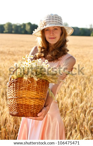 Young woman with basket full of ripe ears wheat and daisies in the wheat field on a sunny day - stock photo