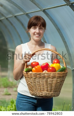 Young woman with basket of harvested vegetables in greenhouse - stock photo