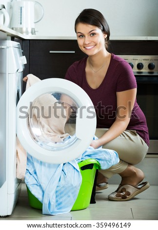 Young woman with basket of sheets near washing machine indoors - stock photo
