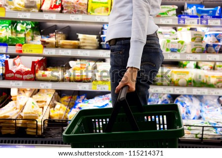 young woman with basket walking in supermarket - stock photo