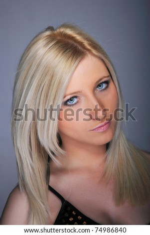 Young woman with beautiful blond hair, posing over gray background
