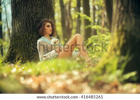 Young woman with beautiful face and straight body in soft knitted cloth holding cute white small goat in sunny forest