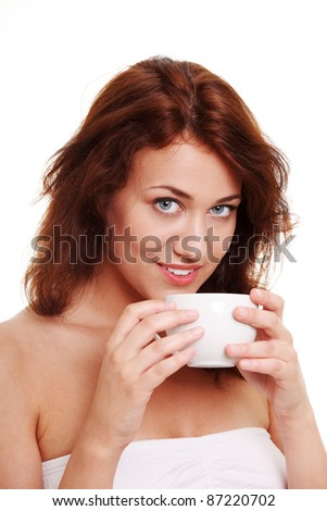 Young woman with beautiful face is having her tea/coffee - stock photo