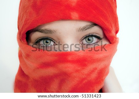 Young Woman with Beautiful Green Eyes covered with red shawl - stock photo