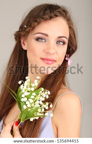 Young woman with beautiful hairstyle and flowers, on grey background - stock photo