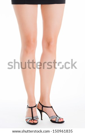 Young woman with beautiful legs standing in elegant dress. Only the legs are visible. She is wearing glamorous high heels. Legs are together. - stock photo