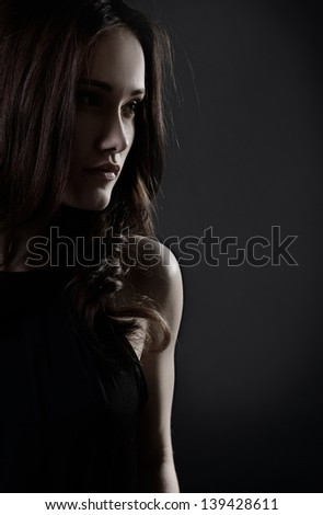 Young woman with beautiful long brown hair posing at studio, profile over black background, toned