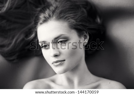 Young woman with beautiful long curly hair -on black and white background - stock photo