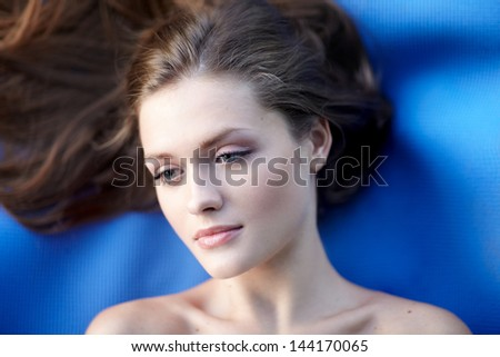 Young woman with beautiful long curly hair -on blue background - stock photo
