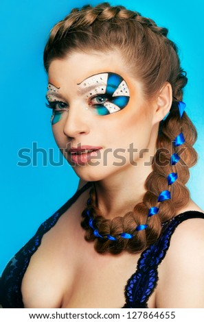 Young woman with beautiful makeup and a blue ribbon in pigtails