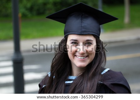 Young woman with beautiful smile in graduation gown. - stock photo