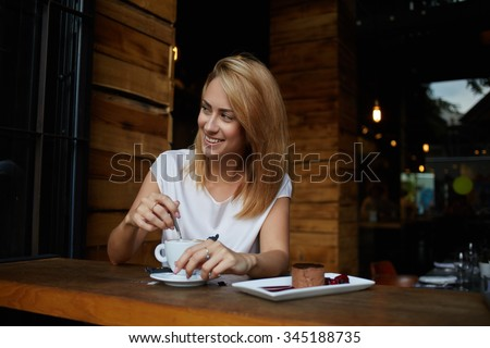 Young woman with beautiful smile looking away while sitting in cafe during coffee break, happy charming hipster girl relaxing in modern cafe, female enjoying good day during morning breakfast in bar  - stock photo