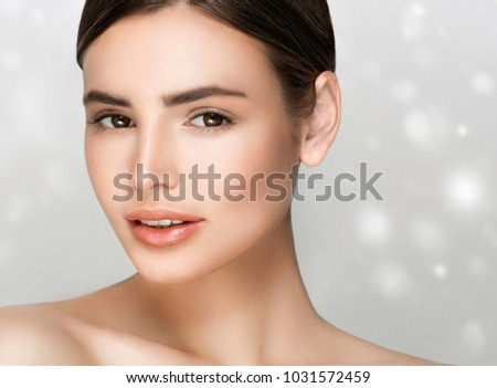 Young woman with beauty skin and beauty hairstyle over gray background. Studio shot.