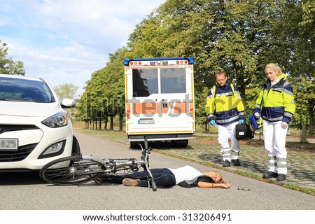 Young Woman with bicycle accident and coming paramedics doctors  - stock photo