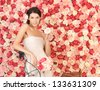 young woman with bicycle and background full of roses - stock photo