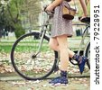 Young woman with bicycle in the park - stock photo