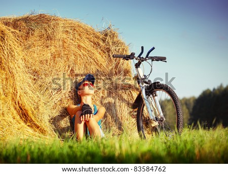 Young woman with bicycle sitting near straw heap and looking to a sky - stock photo