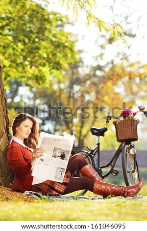 Young woman with bicycle sitting on a grass and reading a newspaper in a park - stock photo