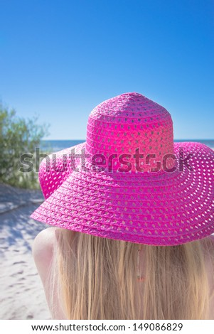 Young woman with big pink hat on the beach  - stock photo