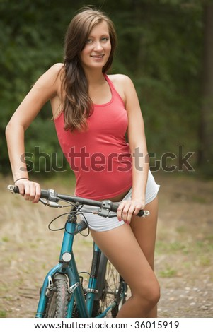 young woman with bike in a natural outdoor setting