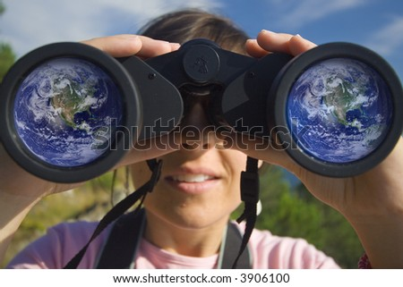 young woman with binoculars with the earth globe reflected in the lens