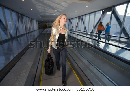 young woman with black bag going on the travelator in a long corridor in a hurry