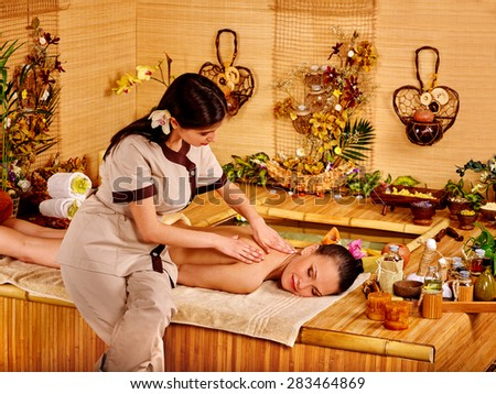Young woman with black hair getting massage in bamboo spa. Two person. - stock photo