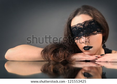 young woman with black lace on her eyes