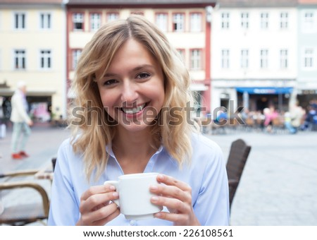 Young woman with blond hair loves coffee