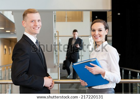 Young woman with blue binder and her workmate