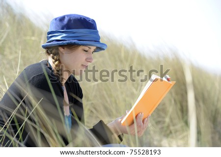 young woman with blue hat reading a book in the dunes - stock photo