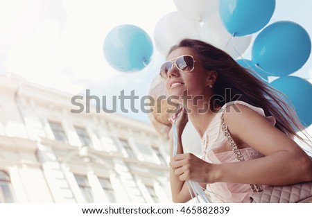 Young woman with blue latex balloons. Outdoors, lifestyle. (soft focus)