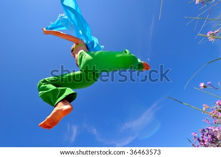 young woman with blue scarf jumping