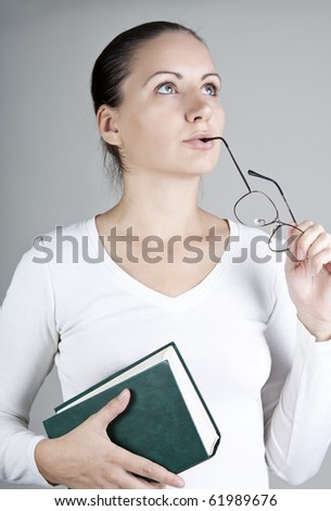 Young woman with book and glasses, thoughtfully looking up, on gray background - stock photo