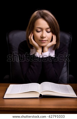 young woman with book at the desk on black background - stock photo