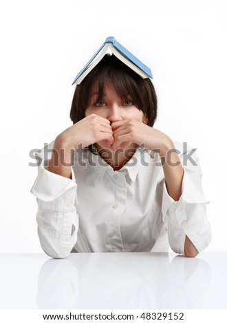 young woman with book on her head, sitting bored of reading - stock photo