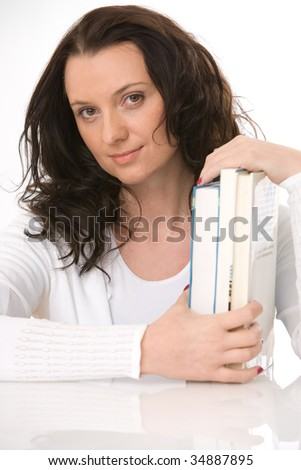 young woman with books sitting at table - stock photo