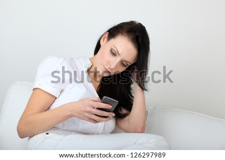 Young woman with bored expression looking at message on her cell phone - stock photo