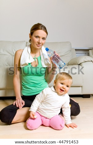 Young woman with bottle of mineral water exercising and her baby girl - stock photo